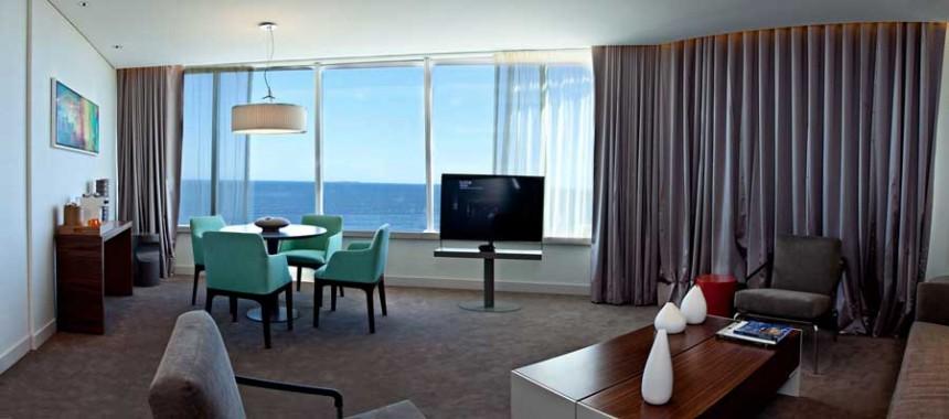 Las habitaciones del Hotel The Grand cuentan con muebles de diseño y grandiosos vistas al mar desde sus grandes ventanas.